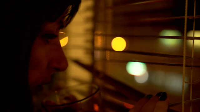 portrait of Girl With Cup of Coffee or tea near dark night window. View on city town with bokeh light. Reflection in glass. Woman drink tea