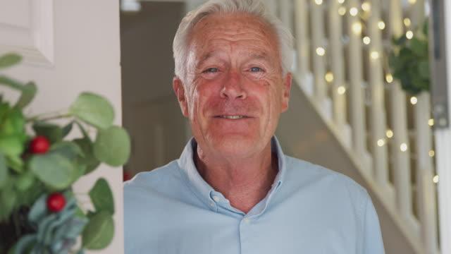porträtt av farfar öppnar dörren och hälsning familj på juldagens morgon - ytterdörr bildbanksvideor och videomaterial från bakom kulisserna