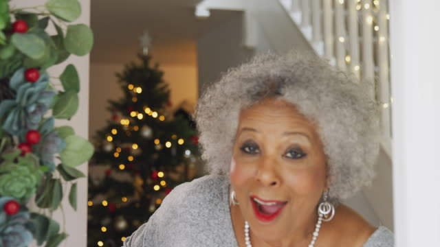 Portrait Of Grandmother Opening Front Door And Greeting Family On Christmas Morning Grandmother at home opens front door and welcomes family visiting on Christmas day - shot in slow motion front door stock videos & royalty-free footage
