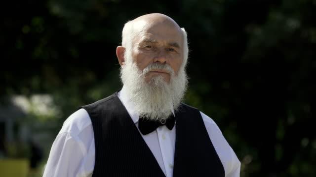 Portrait of gray-haired bearded senior man video