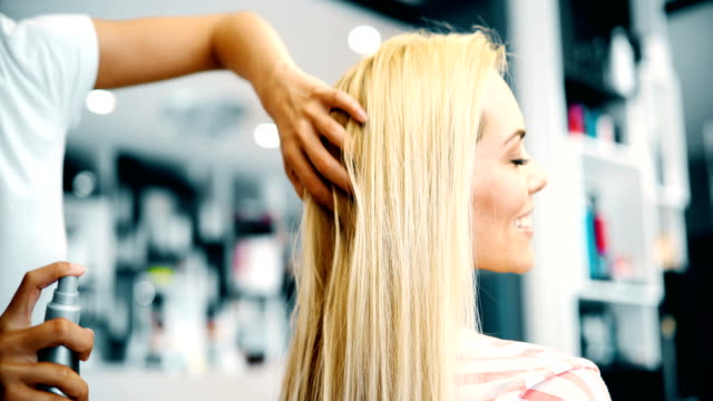 Portrait of hairdresser taking care of blonde woman video