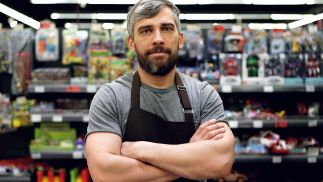 Portrait of handsome bearded guy experienced salesman in apron standing in toy department in supermarket, looking at camera and smiling. Shop and people concept. Portrait of handsome bearded guy experienced salesman in apron standing in toy department in supermarket, looking at camera and smiling. Shop, profession and people concept. owner stock videos & royalty-free footage