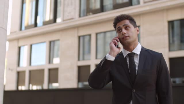stockvideo's en b-roll-footage met portret van knappe zakenman met telefoongesprek - four lawyers
