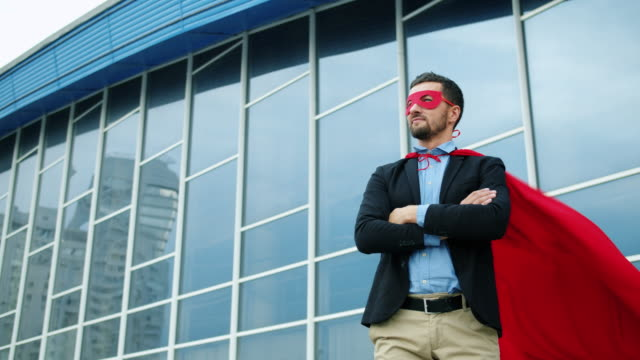 Portrait of handsome businessman in suit wearing superman costume outdoors Portrait of handsome young businessman in suit wearing superman costume outdoors standing alone near office building, red cape is wavering in the wind. cape garment stock videos & royalty-free footage