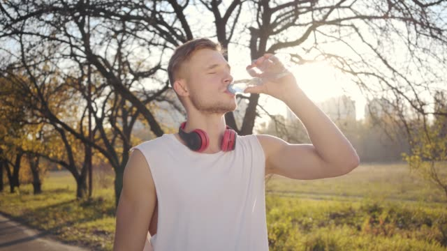 vídeos de stock e filmes b-roll de portrait of handsome caucasian athletic boy drinking water in sunlight and smiling. young sportive boy training outdoors on sunset. sport concept, healthy lifestyle. - campeão desportivo
