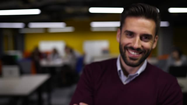 Portrait of handsome coworker in modern office Young, handsome businessman sitting on his desk in modern office space, with crossed arms smiling and looking at camera handsome people stock videos & royalty-free footage