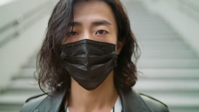 Portrait of handsome fashionable young man with black protective face mask A portrait of a handsome fashionable young man with a black protective face mask. handsome people stock videos & royalty-free footage