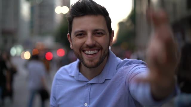 vídeos de stock, filmes e b-roll de retrato do homem considerável na cidade que convida povos para vir - povo brasileiro
