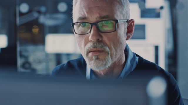 Portrait of Handsome Middle Aged Engineer Wearing Glasses Works on Personal Computer. In the Background High Tech Engineering Facility