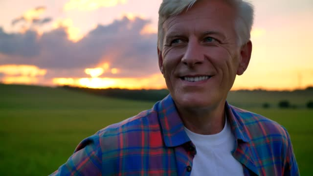 Portrait of handsome old man smiling and looking at camera, standing on wheat field, beautiful view with sunset in background Portrait of handsome old man smiling and looking at camera, standing on wheat field, beautiful view with sunset in background. close to stock videos & royalty-free footage