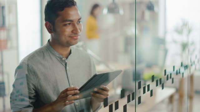 Portrait of Handsome Professional Indian Man Uses Touch Screen Digital Tablet Computer, Writes Important Email, Smiles Charmingly. Successful Man Working in Bright Diverse Office