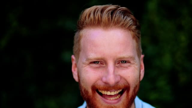Portrait of handsome redhead man smiling Handsome man looking at camera and smiling outdoors. redhead stock videos & royalty-free footage