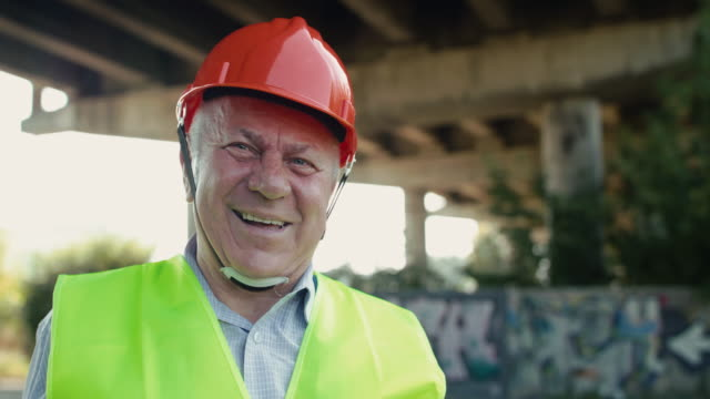 Portrait of handsome senior railroader smiling into camera at railway in summer video