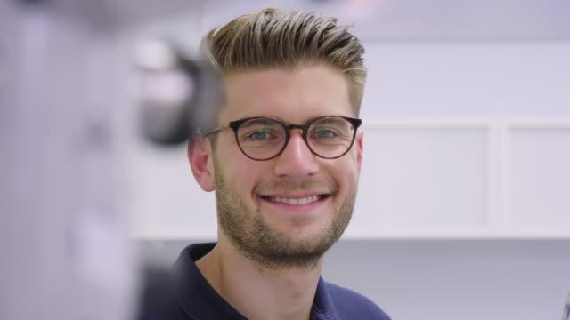 hastanede yakışıklı gülümseyen dişçi portre - diş sağlığı stok videoları ve detay görüntü çekimi
