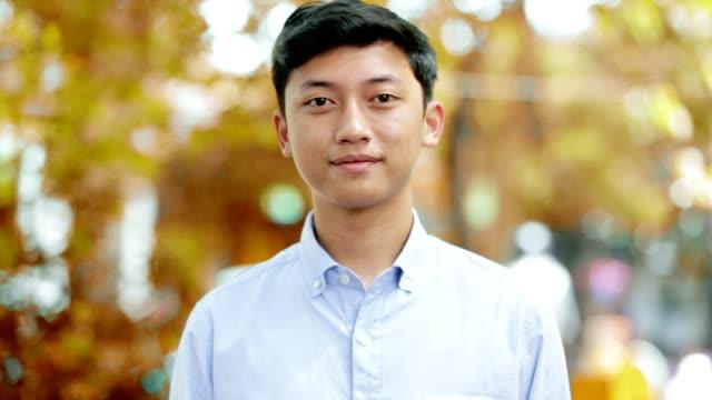 ハンサムなの東南アジア幸せな若い男笑顔して、笑いのトーンの 3 種類の公園でカメラの肖像画 - インドネシア点の映像素材/bロール