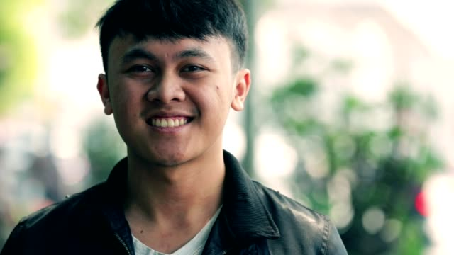 portrait of handsome south east asian young man smiling on camera with three kind of tones (cyan - orange, contrast, and raw) - sud est video stock e b–roll