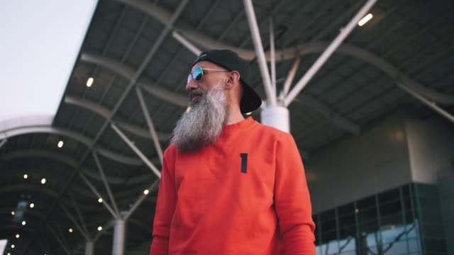 portrait of handsome stylish mature man with long gray beard wearing cap and sunglasses on urban background - lungo video stock e b–roll