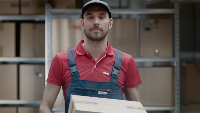 stockvideo's en b-roll-footage met portret van knappe magazijnmedewerker in uniform geeft kartonnen doos pakket en glimlacht. - warehouse worker