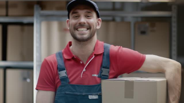 stockvideo's en b-roll-footage met portret van knappe magazijnmedewerker in uniform houdt kartonnen doos pakket en glimlacht. - warehouse worker