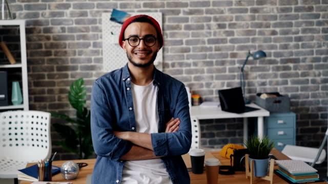 vídeos de stock e filmes b-roll de portrait of handsome young man entrepreneur standing in workplace smiling - homem casual standing sorrir