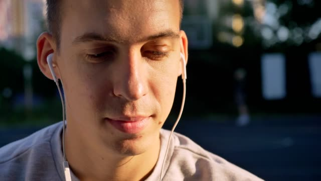 Portrait of handsome young man listening music through earphones and looking at camera, people playing in background open air Portrait of handsome young man listening music through earphones and looking at camera, people playing in background open air. charming stock videos & royalty-free footage