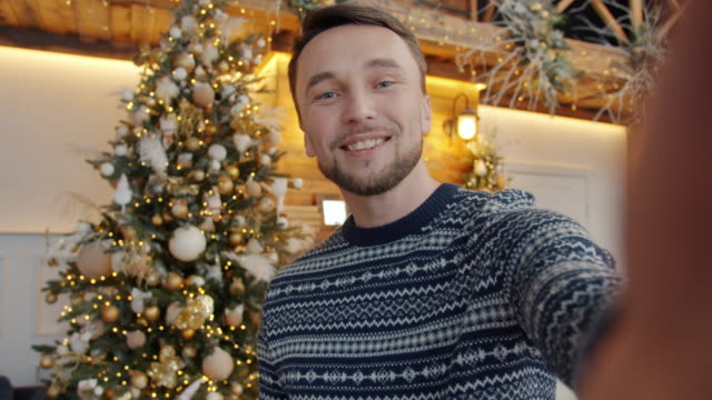 Portrait of handsome young man making online video call on Christmas day talking holding camera video
