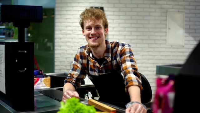 Portrait of handsome young man working at cash register in supermarket, posing looking at camera and smiling happily. Sitting at the cash register video