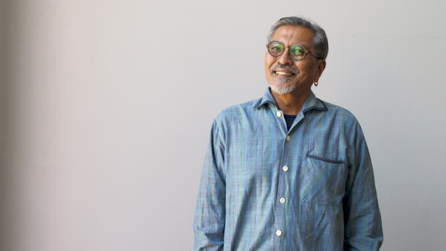 portrait of happy asian senior man wearing glasses and looking at camera isolated on grey background - etnia malese video stock e b–roll