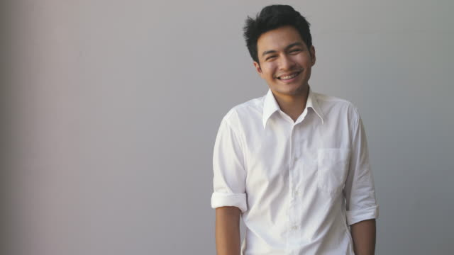 portrait of happy asian young man wearing a white shirt looking at camera isolated on grey background - etnia malese video stock e b–roll