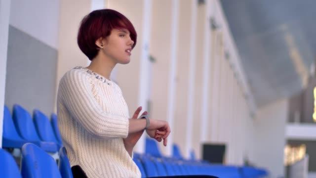 portrait of happy beautiful pink-haired girl sitting on stadium and looking at watch. - krótkie włosy filmów i materiałów b-roll