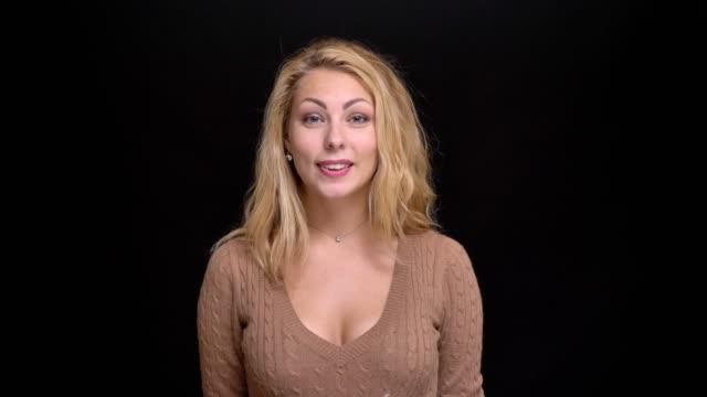 vidéos et rushes de portrait de femme aux longs cheveux caucasienne heureuse regarder joyeusement dans l'appareil photo sur fond noir. - décolleté