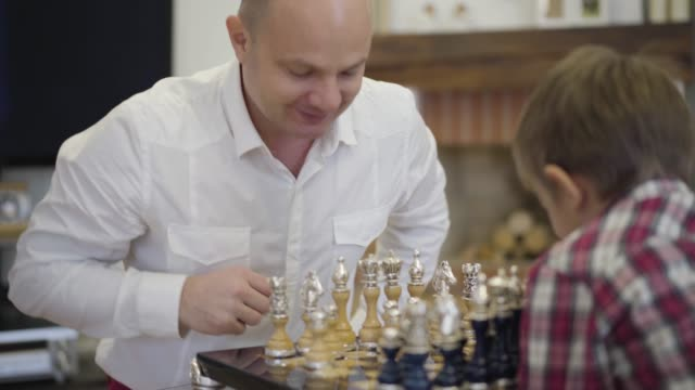 Portrait of happy Caucasian man playing chess with son. Smiling intelligent father educating child at home. Family, intellect, unity.