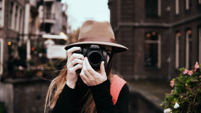 portrait of happy caucasian woman with a camera. attractive cheerful lady in stylish hat taking a picture 4k front view - fotografika filmów i materiałów b-roll