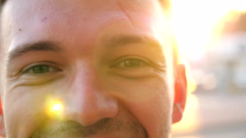 vídeos de stock e filmes b-roll de portrait of happy confident man looking into camera against the background of cars parking. close up of young handsome human standing at urban environment and smiling on sunset. - primeiro plano