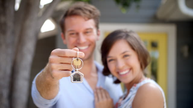 Portrait Of Happy Couple Standing Outside New Home With Keys video
