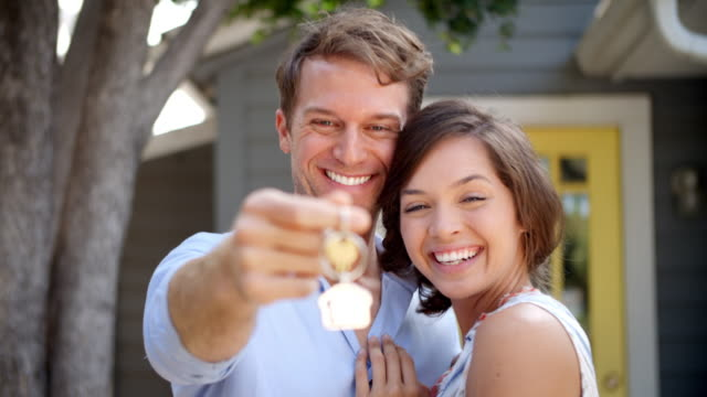 portrait of happy couple standing outside new home with keys - new home stock videos and b-roll footage
