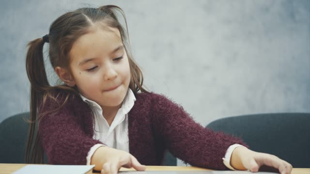 vídeos de stock e filmes b-roll de portrait of happy cute smart girl sitting with stack of books and laptop at table, copy space. education and development concept - girl study home laptop front