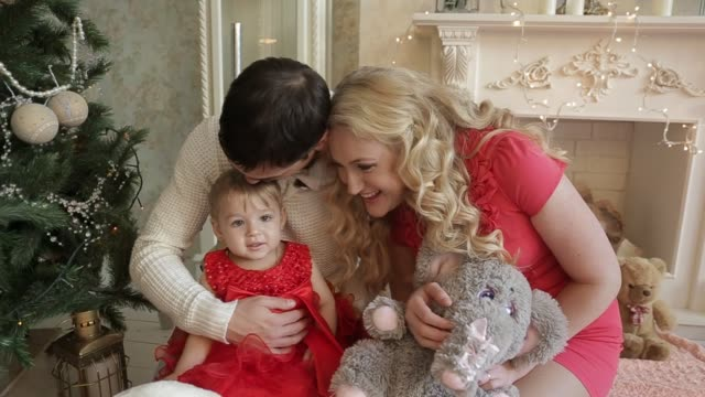 Portrait of happy family celebrates New Year at home on background of decorated Christmas tree and fireplace, look at camera, smile, laugh and hold gift plush toy