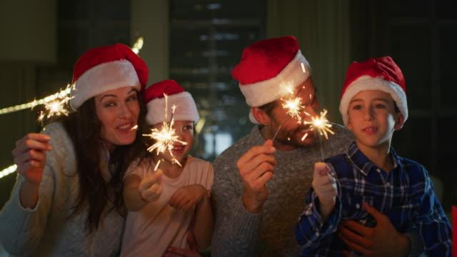 stockvideo's en b-roll-footage met portret van gelukkige familie vieren kerst zingen met santa hoeden in de avond. - christmas family