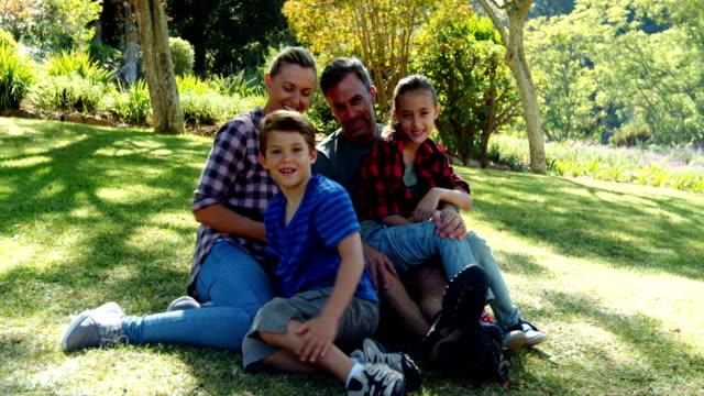 Portrait of happy family sitting in park 4k video