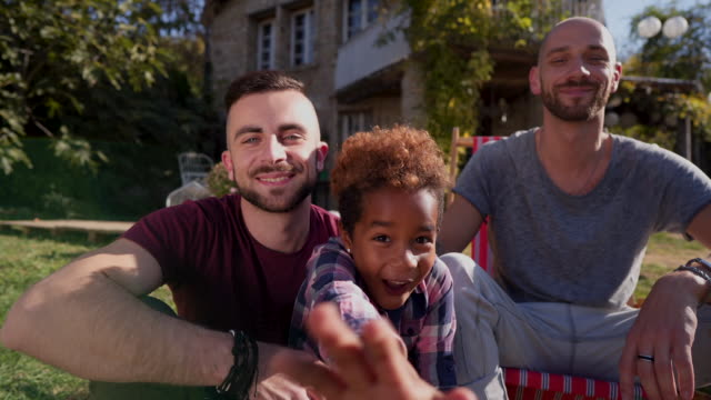 Portrait of happy family Male couple on a city break with their daughter mixed race person stock videos & royalty-free footage