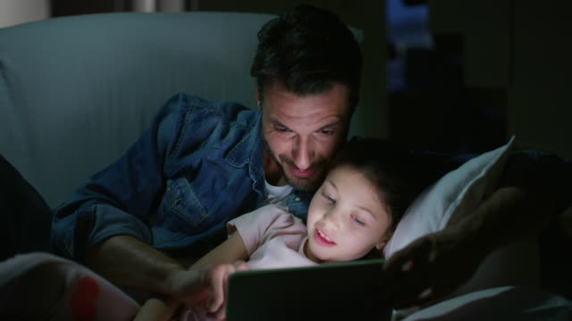 portrait of happy father and daughter using a tablet on sofa in the evening in slow motion. - padre single video stock e b–roll