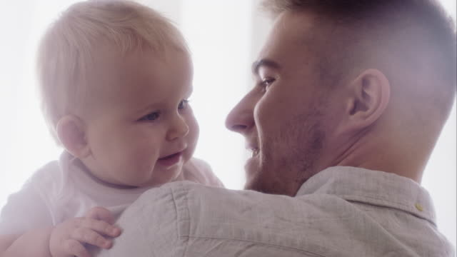 Portrait of happy father holding on hands his baby video