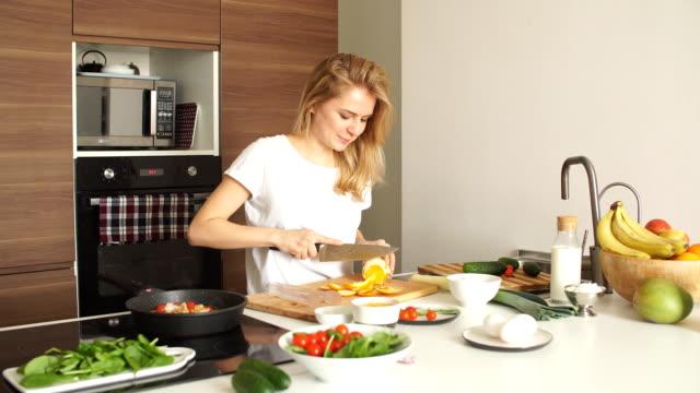 stockvideo's en b-roll-footage met portret van gelukkig vrouwelijke vrouw in wit t-shirt koken diner op keuken - wit t shirt