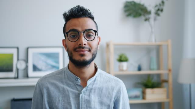 ritratto di felice ragazzo arabo di bell'aspetto sorridente e guardando la macchina fotografica a casa - barba peluria del viso video stock e b–roll