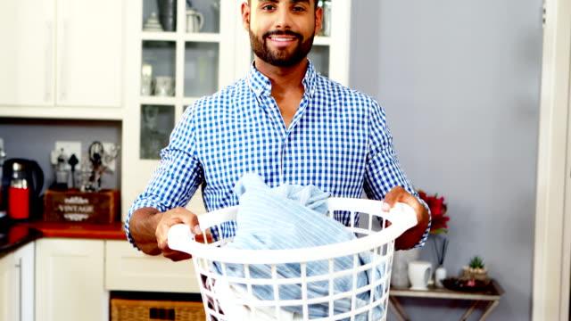 vídeos de stock, filmes e b-roll de retrato de homem feliz, segurando o balde cheio de roupas 4k - afazeres domésticos