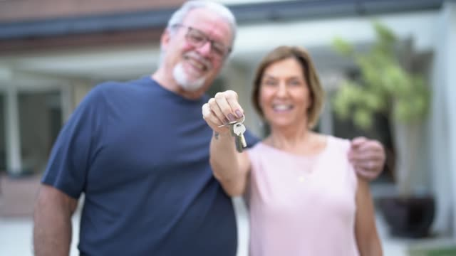 portrait of happy mature couple showing keys of their new house - klucz filmów i materiałów b-roll
