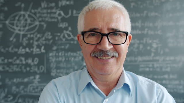 Portrait of happy mature man in glasses looking at camera smiling near chalkboard video