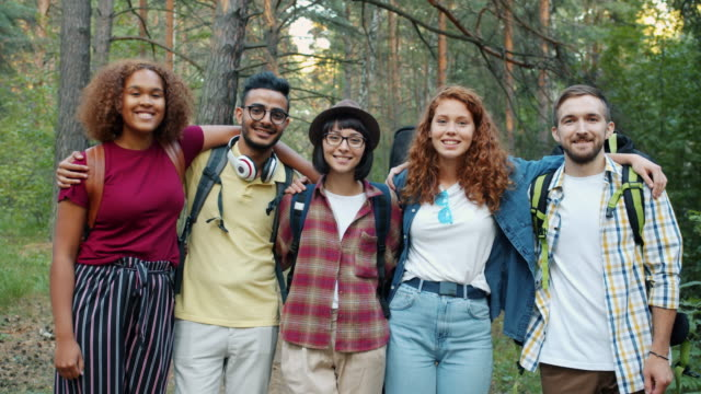 Portrait of happy men and women hugging looking at camera standing in forest video