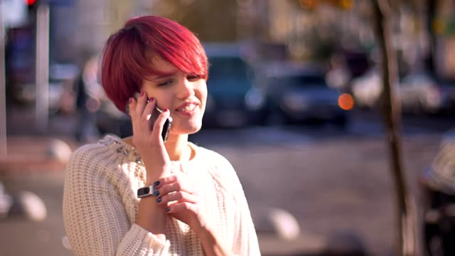 portrait of happy pretty pink-haired girl talking on cellphone on blurred street background. - occhiata laterale video stock e b–roll